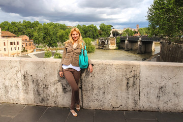 Attractive girl  on the bridge across the Tiber in Rome, Italy