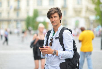 Portrait of young guy sending message with smartphone