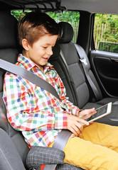 Junge auf Autofahrt mit Ipad