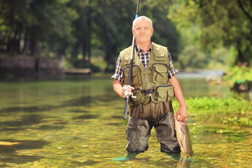 Mature fisherman holding fish in a river