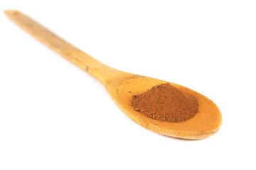 Cinnamon powder on wooden spoon