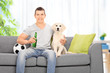 Man sitting with dog on couch at home