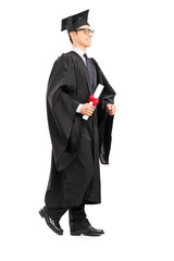 Graduate student walking with diploma in his hand