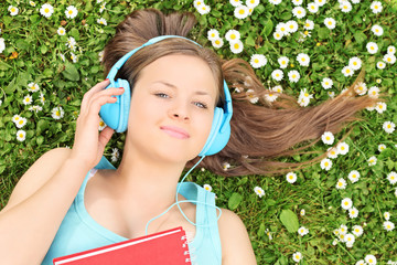Beautiful girl lying in a meadow and listening to music