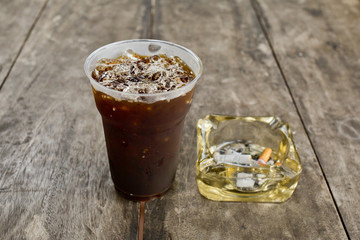 Delicious ice coffee americano  with cigarette on the old wooden