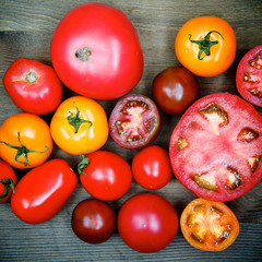 Сolorful fresh tomatoes on wooden background
