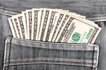 A hundred dollar bills sticking in the back pocket of denim blac