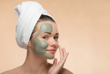 Fototapety Spa girl with a  towel on her head applying facial clay mask and
