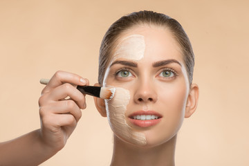 Beautiful girl in spa applying facial cosmetic cream with brush