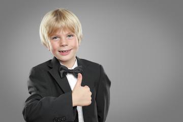 Kind im Anzug mit daumen hoch