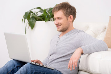 Portrait of happy mature man with laptop in house.