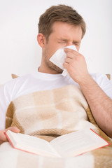 Man blowing his nose while lying sick in bed.