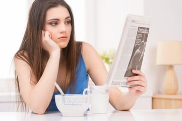 young woman drinking coffee and reading news.