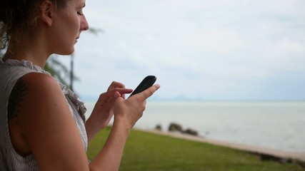 Young Woman with Mobile Phone near the Sea.