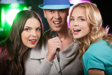 Group of three friends singing with microphone.