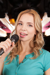 Beautiful blond with microphone standing and singing.