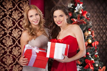 Two happy women holding gift boxes.