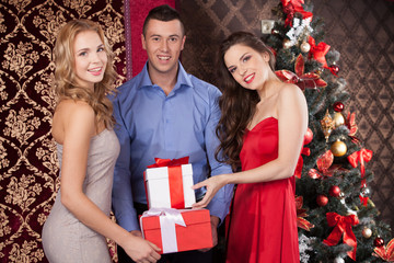 wo happy women and man holding gift boxes.