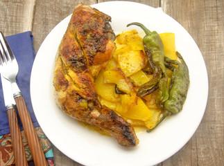Pollo asado con patatas fritas y pimientos