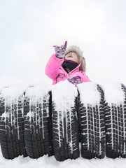Child with tyres in the snow points to the sky