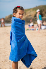 Portrait of young girl on the beach with towel.