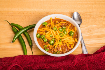 Bowl of Chili with Cheese and Peppers by Red Towel