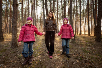 mother and two daughters walking at sunny forest