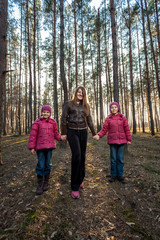 beautiful mother walking with daughters at forest