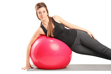 Girl exercising with pilates ball on exercise mat