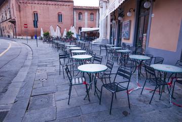 Fila di tavolini e seggiole vuoti, caffe, gelateria, bar