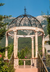 Beautiful delicate gazebo in  park on  background of mountains