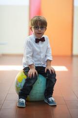 Little student at school sitting on globe