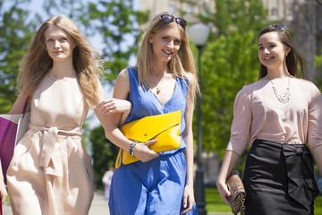 Three beautiful fashion women walking on the street
