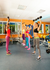 Instructor and three young women exercising