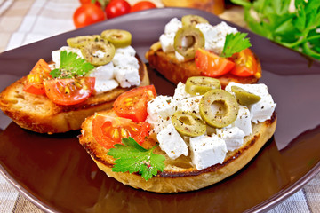 Sandwich with feta and olives on tablecloth