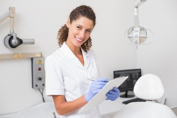 Dental assistant writing in clipboard