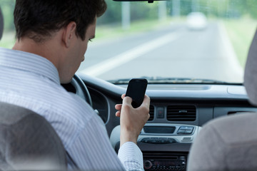 Man texting on mobile phone during driving a car