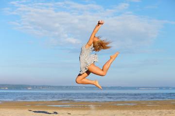 Beautiful young girl jumping on sea