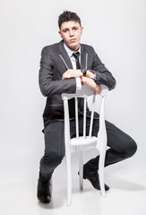 young man in classic suit sitting on white wooden chair at studi