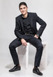 latin man in black suit sitting on white chair and smiling