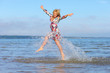 canvas print picture - Beautiful young girl jumping on sea
