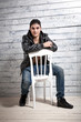 man in jeans and jacket sitting on chair against wooden wall