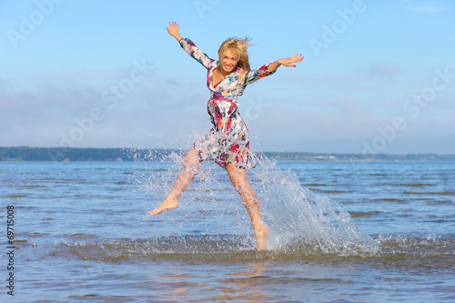 canvas print picture Beautiful young girl jumping on sea