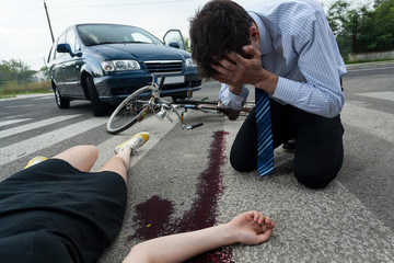 Driver and injured woman at road accident scene