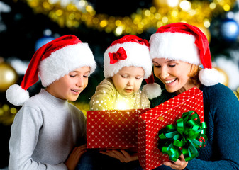 Mother with children opens the box with gifts on the christmas h