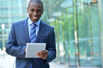 Busines executive smiling with tablet pc