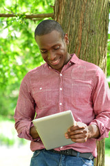Happy middle aged man using tablet in park