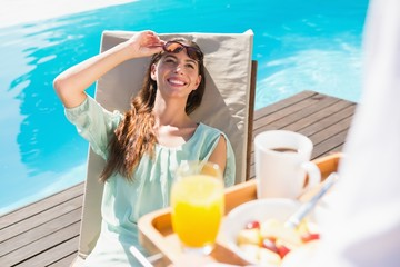 Smiling woman looking at waiter with breakfast tray