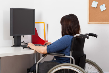 Woman on wheelchair working in office