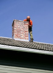 Man on a roof inspecting a chimney